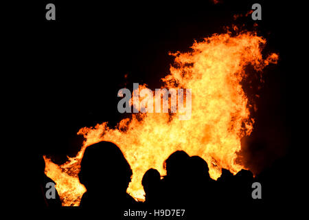General public silhouette against the burning bonfire at Penkridge Scouts Bonfire, Staffordshire, England ,UK, 2016. - Stock Photo