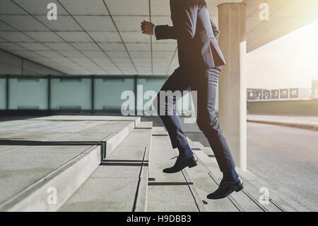 Businessman running fast upstairs. Horizontal outdoors shot. - Stock Photo