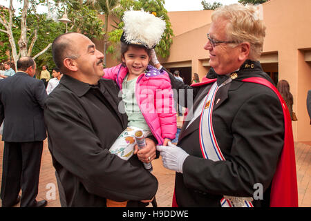 A little girl in her father's arms tries on the plumed hat of an elaborately costumed member of the Knights of Columbus - Stock Photo