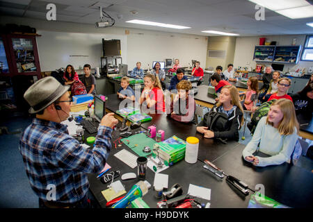 An Asian American science teacher lectures an attentive middle school STEM (Science, Technology, Engineering and - Stock Photo