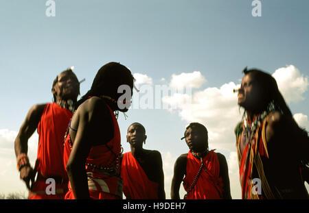 Maasai semi-nomadic people located in Masai Mara National Reserve Kenya Africa. Both men and women wear colorful - Stock Photo
