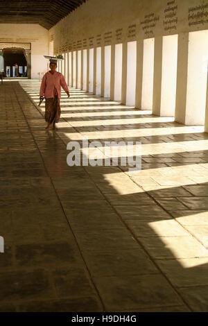 A woman in the walkway to the Shwezigon Pagoda in the town of Nyaung-U near Bagan in Myanmar - Stock Photo