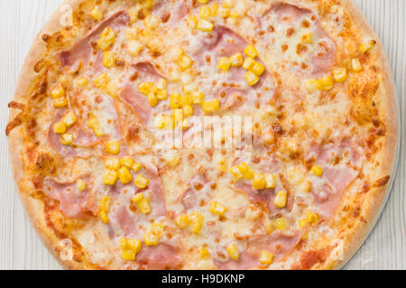 Pizza with ham and corn on the table - Stock Photo