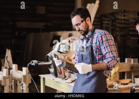 Handsome carpenter in protective glasses standing near his wooden object in the workshop - Stock Photo