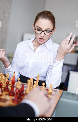 Young businesswoman playing chess with businessman, analyzing situation - Stock Photo