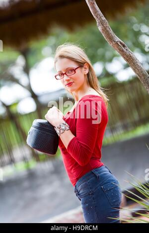 Beautiful teen girl standing with jewel case in hands eyes-contact serious looking at camera attractive good-looking - Stock Photo
