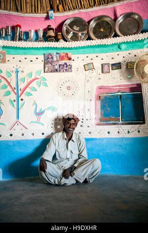 A Meghawal tribal woman standing inside of her family's ornately painted mud brick hut in Hodka, a semi-arid region - Stock Photo