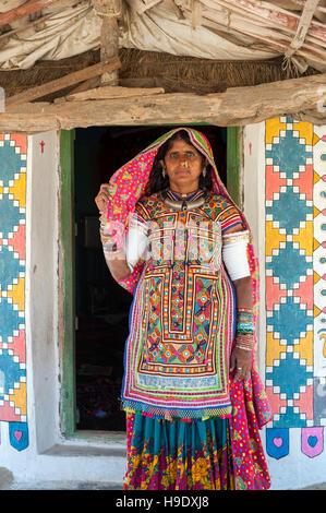 A Meghawal tribal woman standing in front of her family's ornately mud brick hut in Hodka, a semi-arid region bordering - Stock Photo