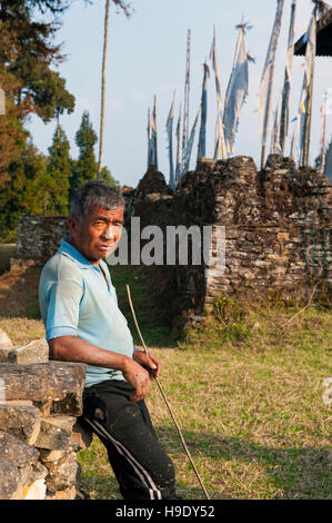 A shepherd rests while grazing his sheep at Rusem Monastery in Sikkim - Stock Photo
