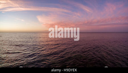 Aerial panorama of sunset over ocean. Nothing but sky, clouds and water. Beautiful serene scene - Stock Photo