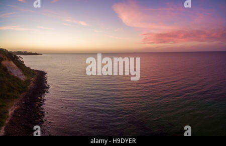 Aerial panorama of magnificent purple sunset over ocean - Stock Photo