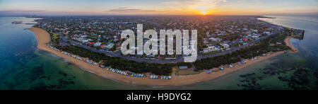 Aerial panorama of sunrise over Brighton suburb, showing iconic beach huts, houses, and the ocean. Melbourne, Victoria, - Stock Photo