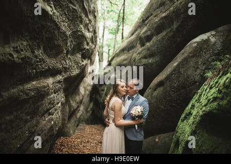 Gorgeous wedding couple kissing and hugging in forest with big rocks - Stock Photo