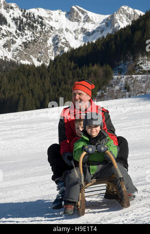 Man and children on a sledge - Stock Photo
