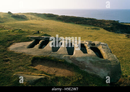 Six body-shaped graves cut in a sandstone outcrop adjacent to St Patrick's Anglo-Saxon chapel on Heysham Barrows, - Stock Photo
