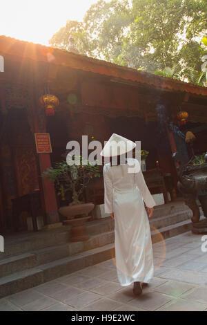 Woman in ao dai dress at Quan Thanh Temple, Hanoi, Vietnam - Stock Photo