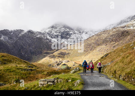Hikers hiking on Miners' Track with snow and low cloud on Mount Snowdon in winter.  Pen-y-Pass Llanberis Gwynedd - Stock Photo