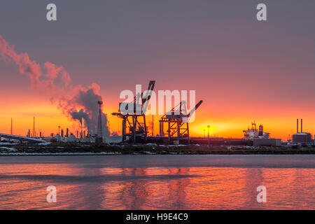 Red skies & setting sun, steam emissions at the docks, cranes, industry, port facilities of South Gare on Teesside, - Stock Photo