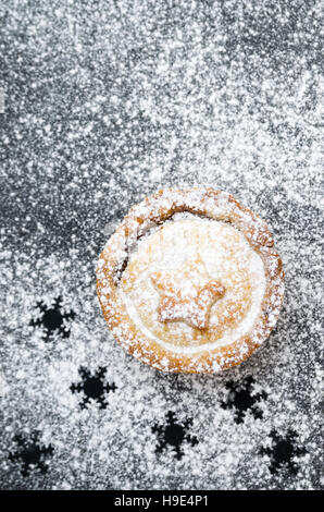 Christmas mincemeat pie, decorated with a star and dusted with icing sugar on slate and gold backgrounds - Stock Photo