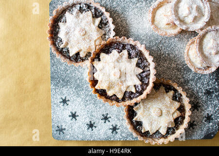 Christmas mincemeat pies, decorated with a star and dusted with icing sugar on slate and gold backgrounds - Stock Photo