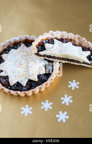 Christmas mincemeat pies, decorated with a star and dusted with icing sugar on a gold background - Stock Photo