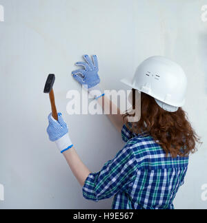 Young woman in casual clothes in front of white wall - Stock Photo