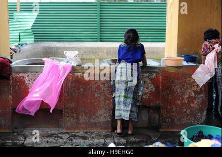 Maya indigenous women wash laundry at the Public Pila of Antigua, Guatemala. - Stock Photo