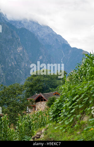 Houses clinging to the mountain in Tiger Leaping Gorge, a scenic canyon on the Jinsha River, Yunnan, China - Stock Photo