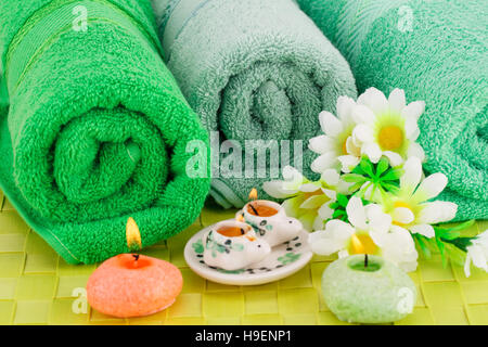 Spa set with towels, candles and flowers on bamboo background. - Stock Photo