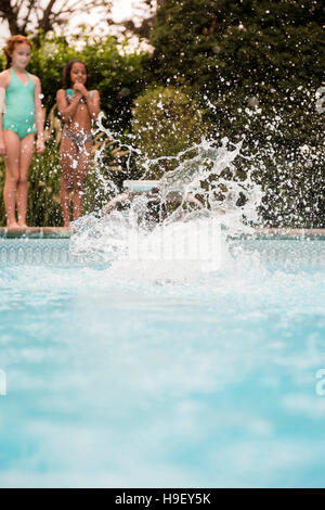Splash from girl jumping into swimming pool - Stock Photo