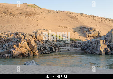Kunene River in front of towering ancient Namib Desert sand dunes of Namibia and Angola - Stock Photo