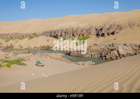 Offroad camping at Kunene River in front of towering ancient Namib Desert sand dunes of Namibia and Angola - Stock Photo