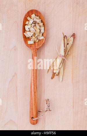 Licorice herbal medicine in wooden spoon, chopped and sliced on - Stock Photo