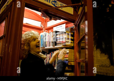 Old red telephone box now used as a book swap with public Wi-Fi available in Beer Devon West Country UK November - Stock Photo