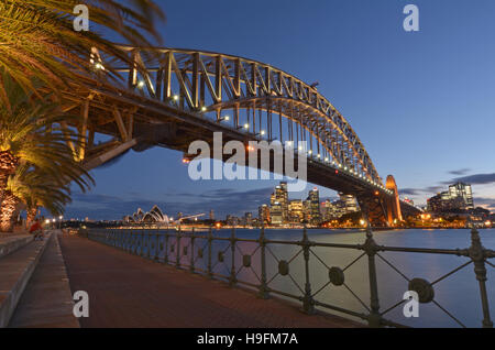 Long exposure of Sydney Harbour Bridge west side and Sydney Skyline at dusk light in Sydney, Australia. - Stock Photo