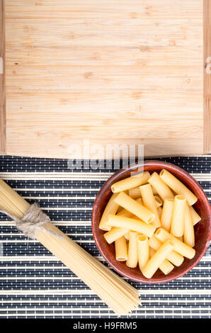 Top view of pasta in a wooden bowl with a bunch of spaghetti next to a wooden plank for cooking on a striped background - Stock Photo