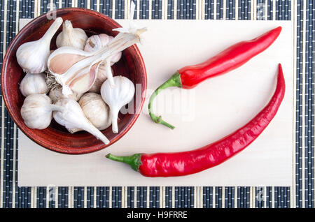 Top view of a spice for cooking - red chilli peppers and garlic in a wooden bowl on a striped background - Stock Photo