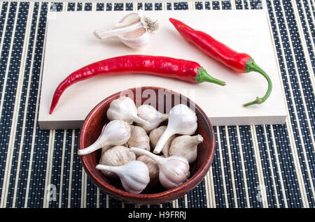Spice background for cooking - cayenne chillies and garlic in a brown bowl on a kitchen table - Stock Photo