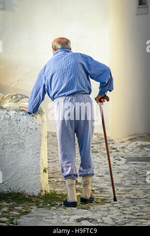 Old tired man with a walking stick shooted from behind elderly concept - Stock Photo