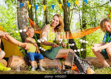 Mother and kids roasting marshmallow over the fire - Stock Photo