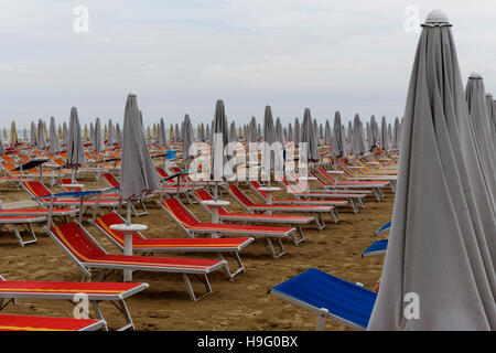 Deck chairs and parasols on the beach, Cervia, Emilia Romagna, Italy - Stock Photo