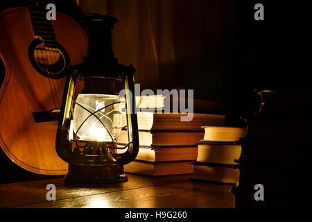 Kerosene lamp, guitar and books on the table - Stock Photo