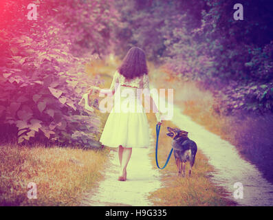 Young bride wearing wedding dress walking barefoot with dog on rural road back to camera. Woman bring wedding shoes. - Stock Photo