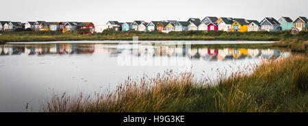 Hengistbury Head beach huts across Christchurch Harbour - Stock Photo