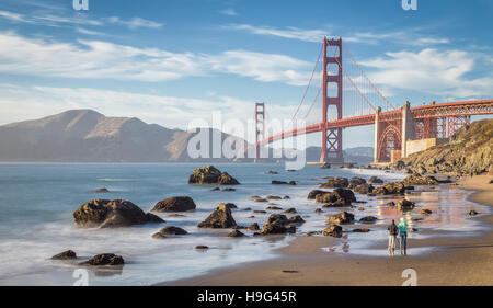 Classic panoramic view of world famous Golden Gate Bridge at sunset seen from Baker Beach, San Francisco, California, - Stock Photo