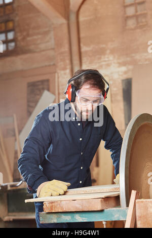 Carpenter with labor protection working on grinding machine - Stock Photo
