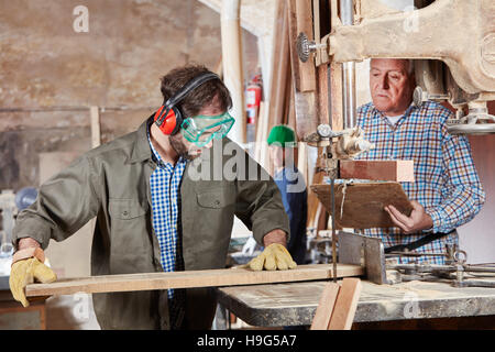 Carpenter cutting wood during apprenticeship - Stock Photo