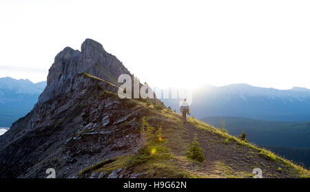 Male hiker walks along ridge of mountain during sunrise - Stock Photo