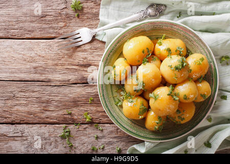 Glazed new potatoes with parsley close-up on the table. horizontal view from above - Stock Photo
