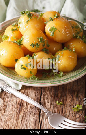 Glazed new potatoes with parsley close-up on the table. vertical, rustic style - Stock Photo